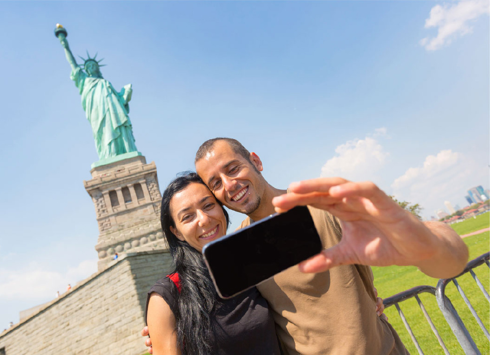 tourist couple taking a selfie in front of statue of liberty