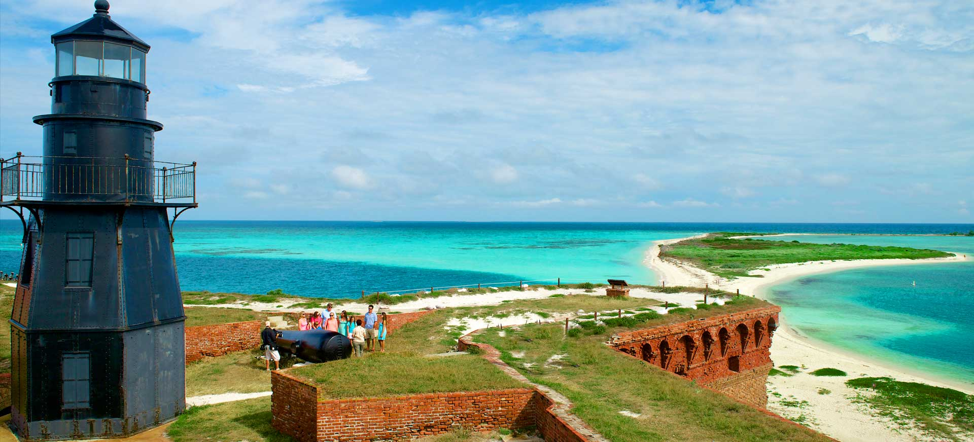 A group touring the grounds of Ft. Jefferson standing next to a cannon as the sea of the Dry Tortugas stretches out before them