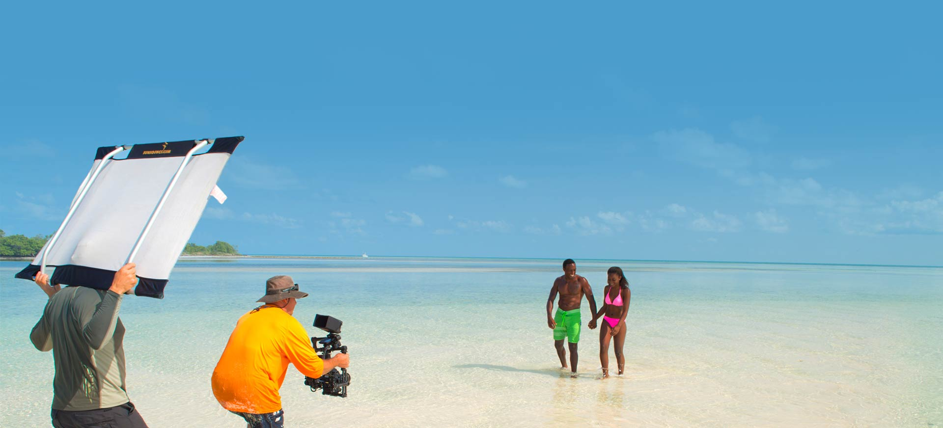 camera man filming two models on a sandbar in key west