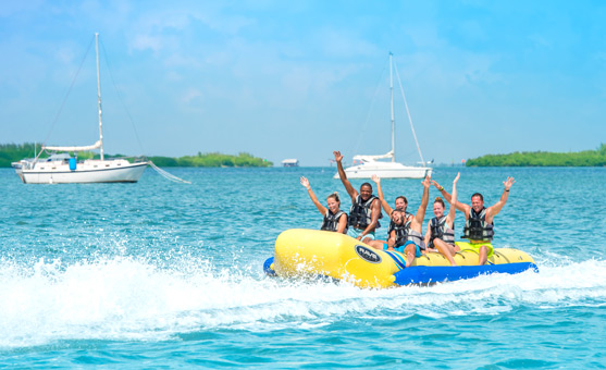Six people with arms jubilanly raised in the air being pulled at high speeds on an inflatable banana boat