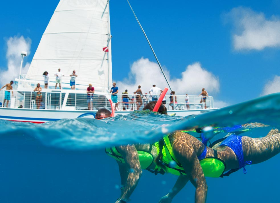 Foreground of a couple in a flotation vest, mask, fins and snorkel swimming in front of a Fury catamaran filled with onlookers