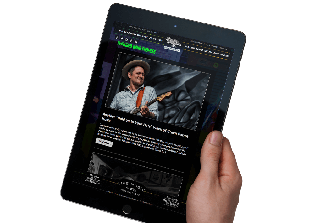 Hand holding tablet that displays the Green Parrot Bar website