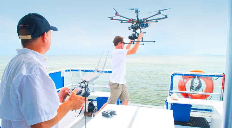 drone being launched by crew off boat