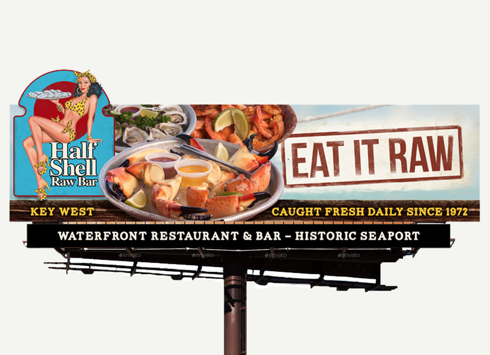 Picture of billboard showing Half Shell Raw Bar Key West logo, pictures of crab legs, shrimp and oysters and the words 'Eat it Raw', 'Caught Fresh Daily Since 1972' and 'Waterfront Restaurant & Bar - Historic Seaport'