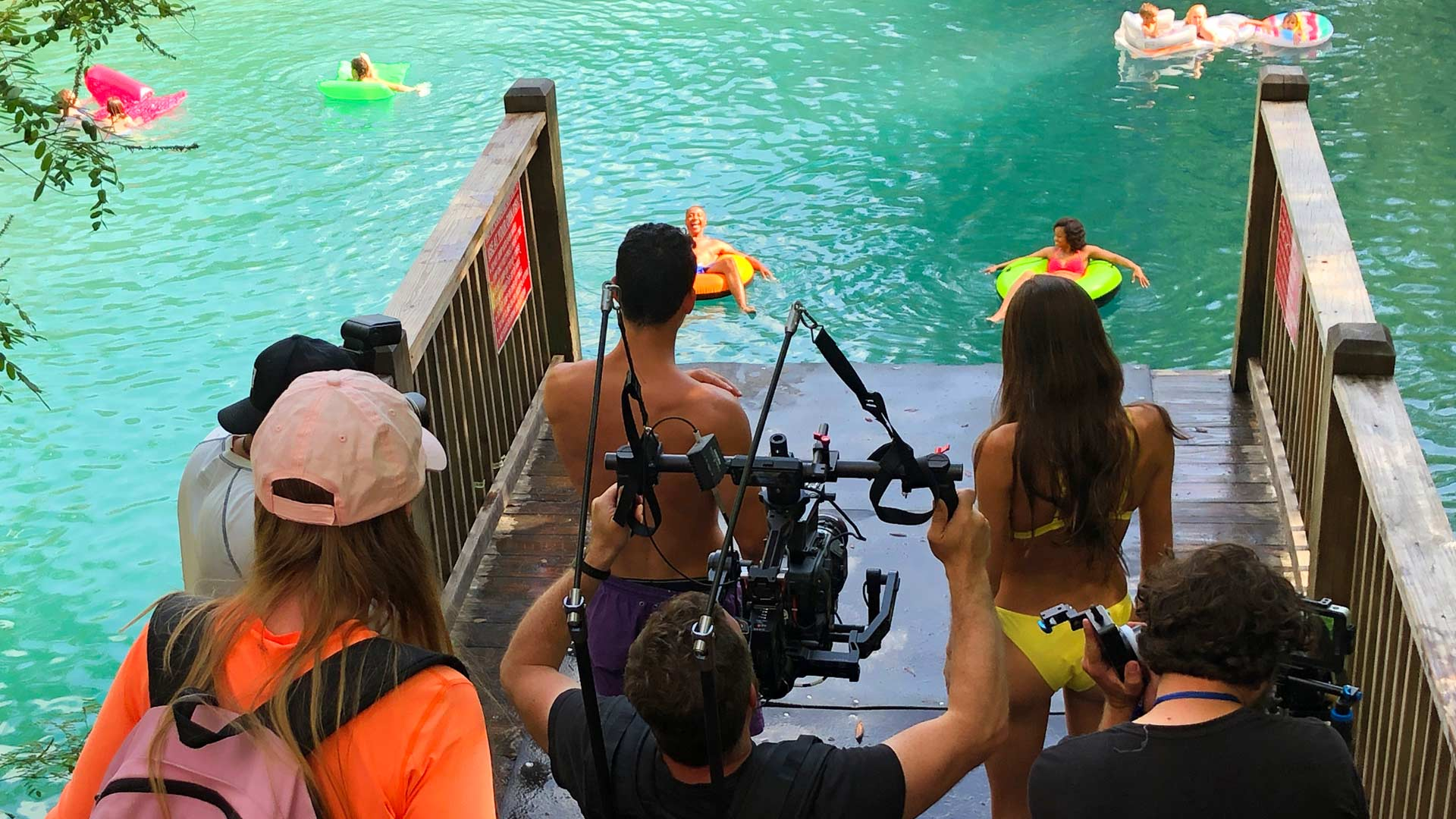 Production team filming couple about to jump into water