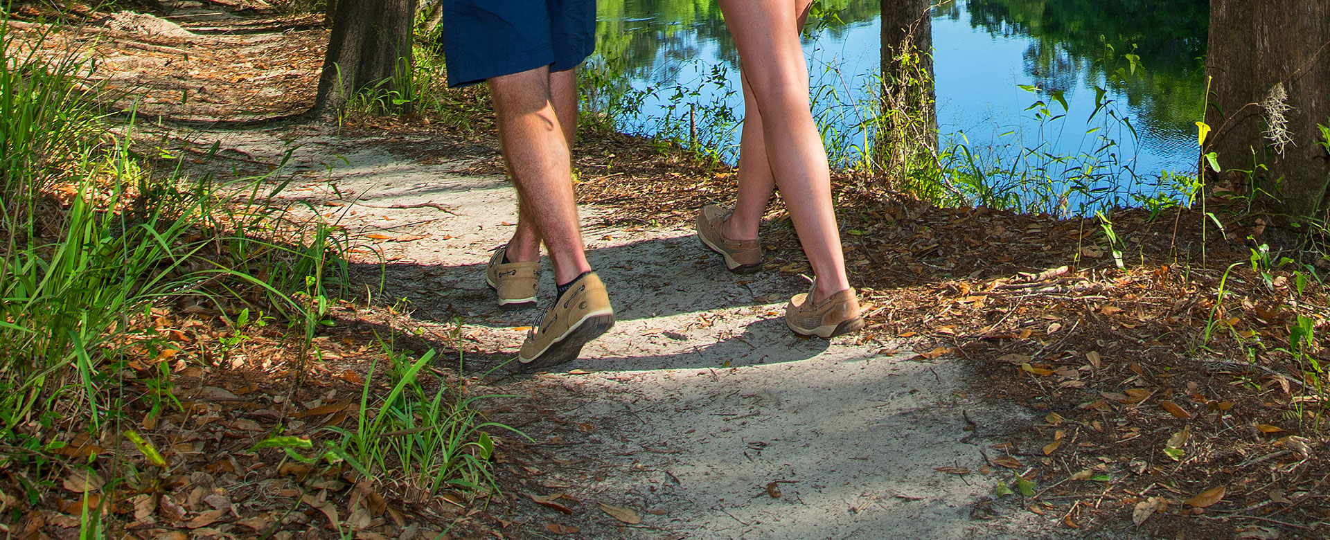 Lower legs of couple hiking by river
