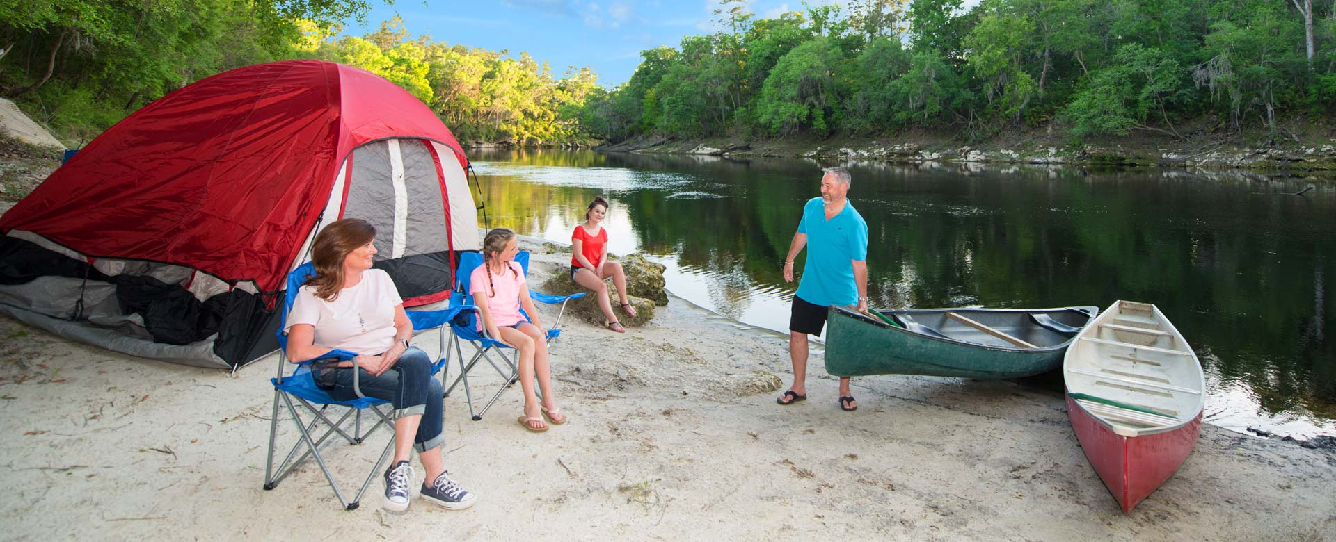 Family camping by water in daytime