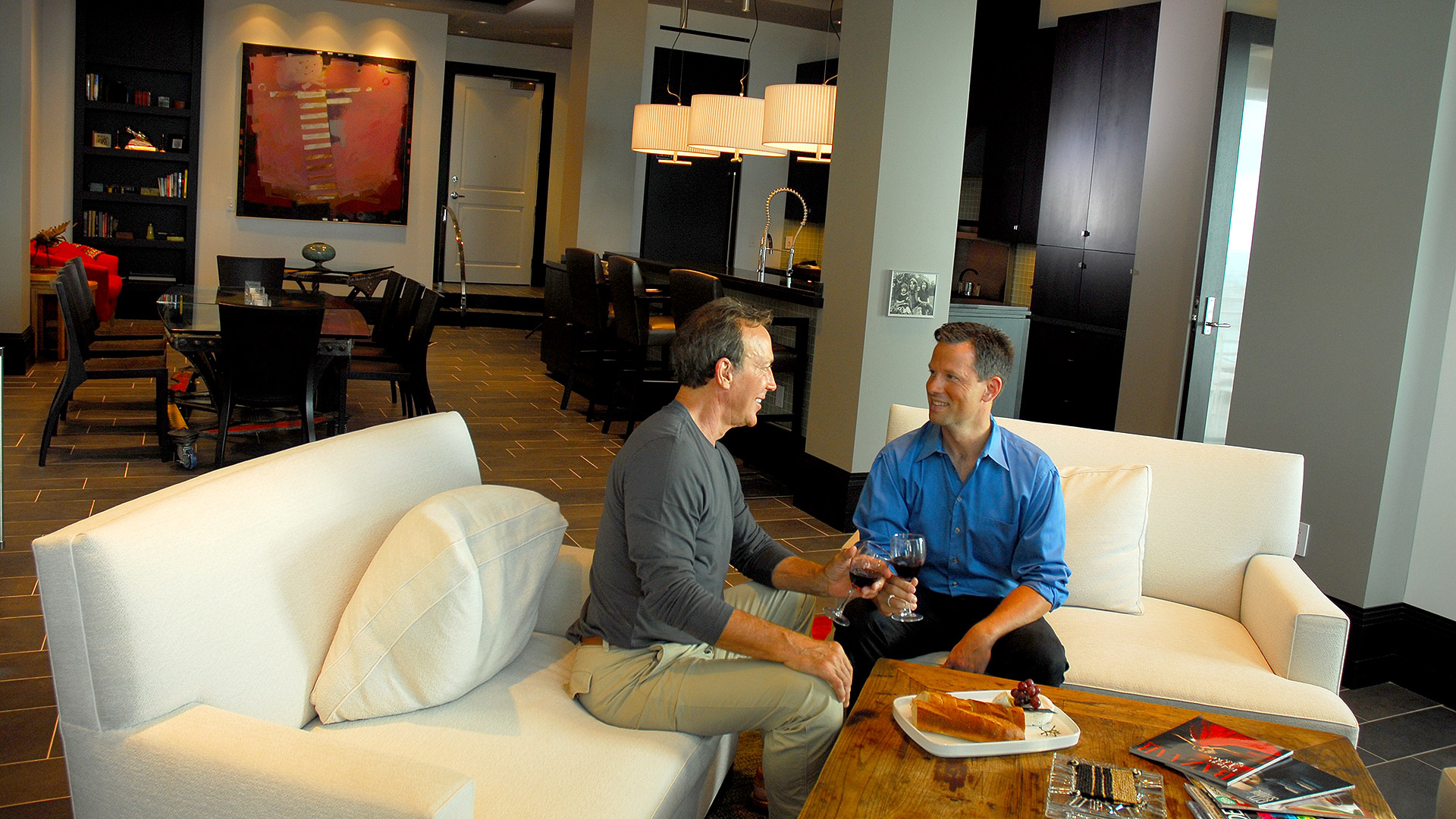 picture of two gentlemen sitting in living room with kitchen and dining area in background