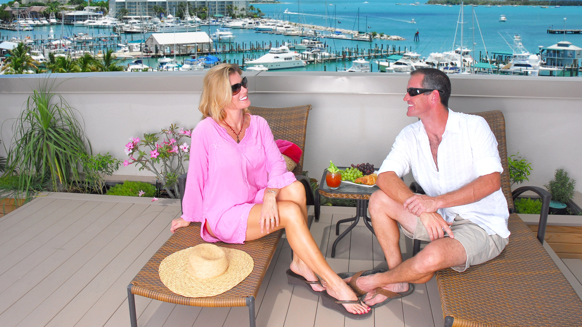 couple sitting outdoors on lounge chairs on rooftop deck with key west harbor and boats in background