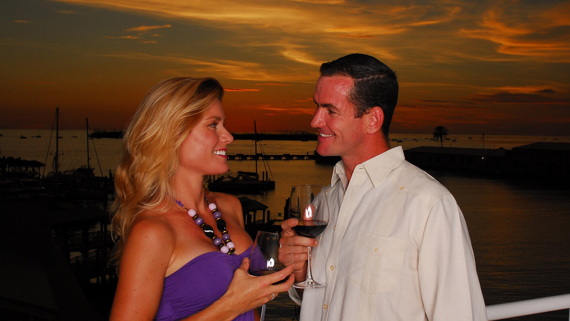 picture of couple outdoors holding wine glasses with key west harbor in background at sunset